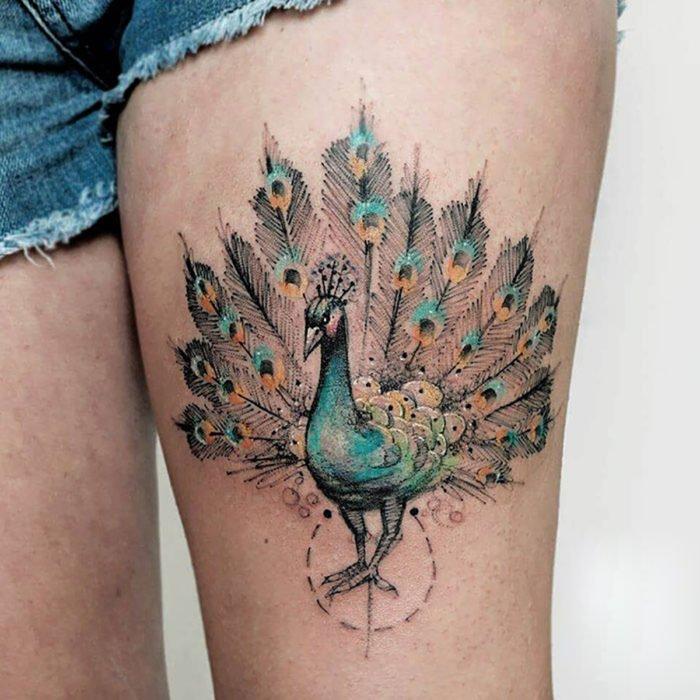 Tatuagem de pavão na perna da mulher