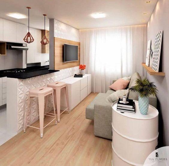 Sala minimalista com sofá cinza, rack branca, painel de TV e prateleiras de madeira.