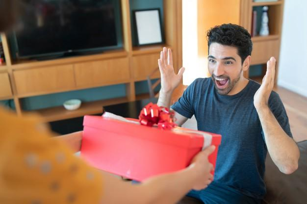 Portrait of a woman surprising her boyfriend with a present. celebration and valentine's day concept. Free Photo