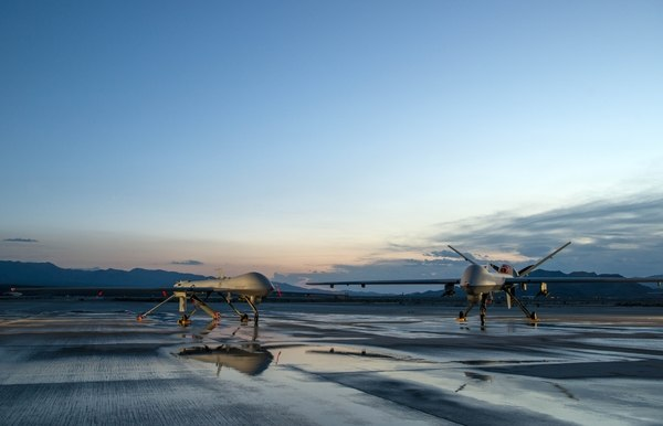 An MQ-1 Predator and an MQ-9 Reaper sit on the airfield at Creech Air Force Base, Nev. (Staff Sgt. Vernon Young Jr./Air Force)