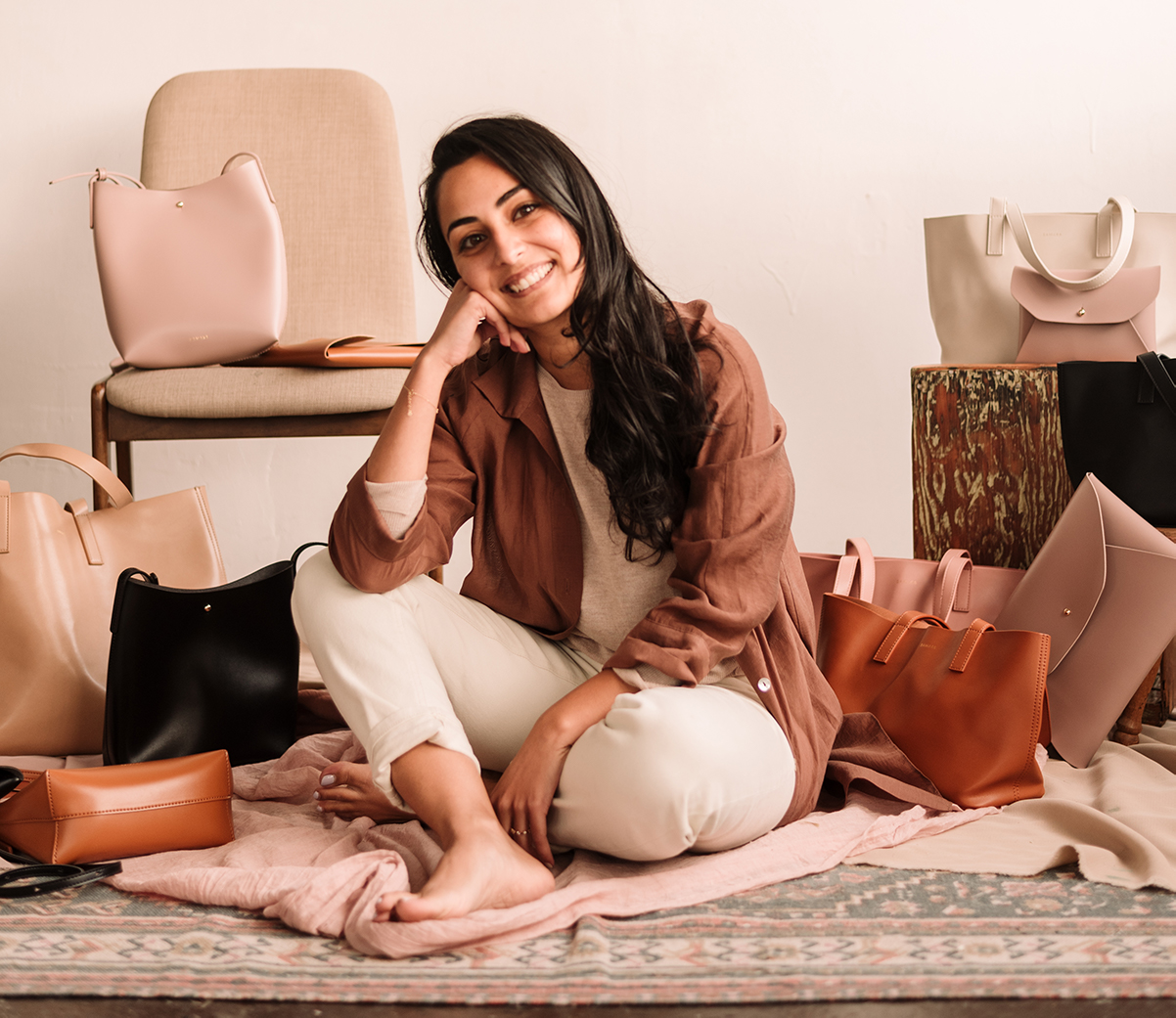 Picture of Salim sitting on the ground with Samara bags
