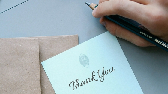 A thank you card and envelope with a person holding a pen poised to write