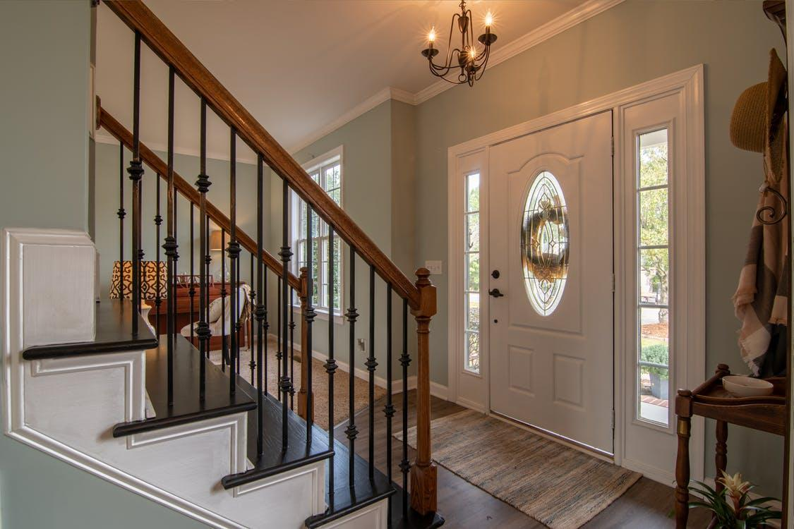 Brown Wooden Staircase With Brass Chandelier
