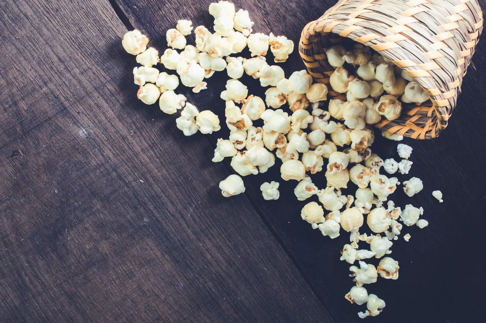 A scattering of popcorn on a wooden background