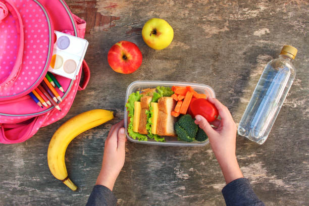 mother preparing healthy food for kids lunch box for her child