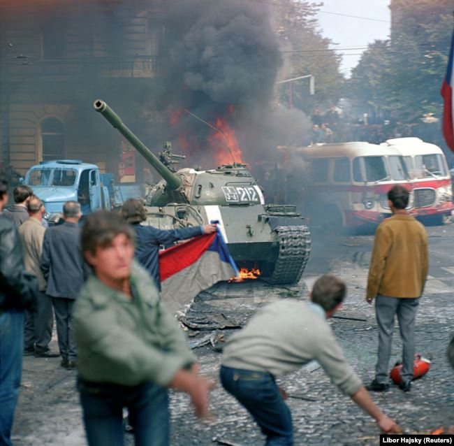 Чехи будують огорожі та атакують радянські танки перед будівлею Чеського радіо у Празі. 1968 рік