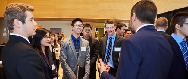 Students smiling at one another at Telfer networking event