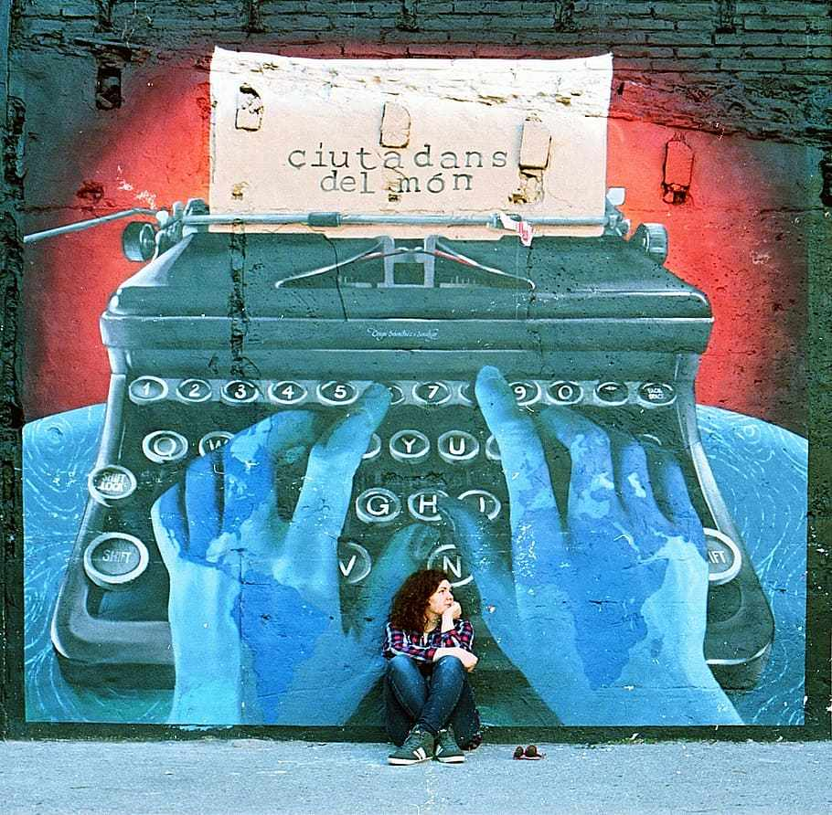 This image has an empty alt attribute; its file name is graffiti-typewriter-young-woman-sitting.jpg