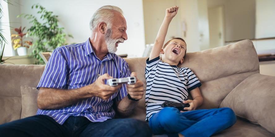 Man and boy on the couch playing console games