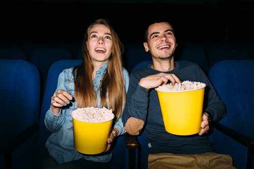 A couple eating popcorn from big yellow containers and watching a movie.