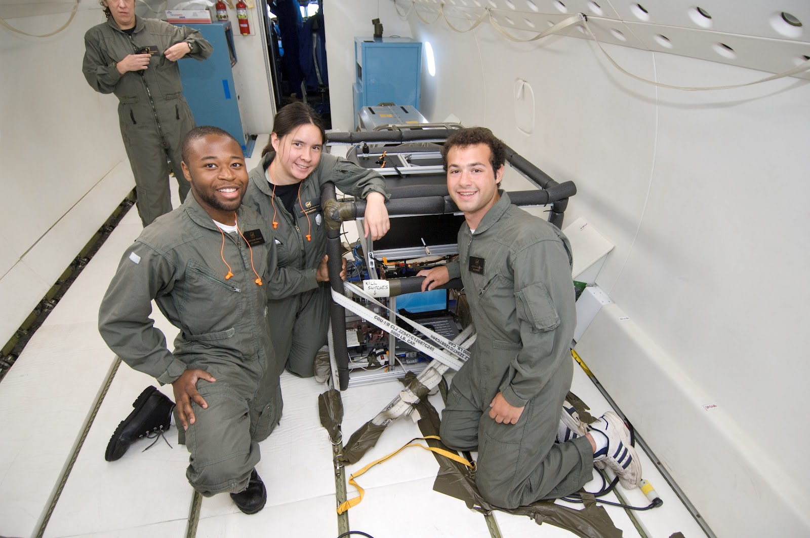 Three people in flight suits inside a white empty airplane cabin with their experiment.