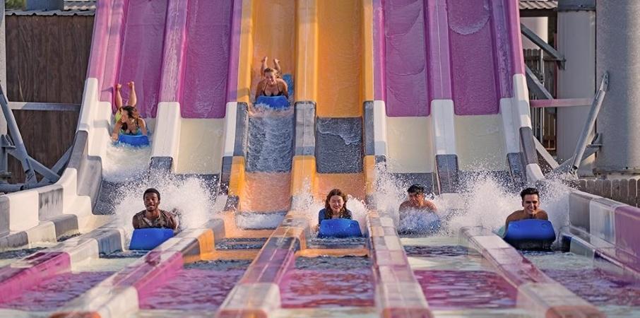 Kids sliding down a water slide at Six Flags Hurricane Harbor in Arlington, TX.