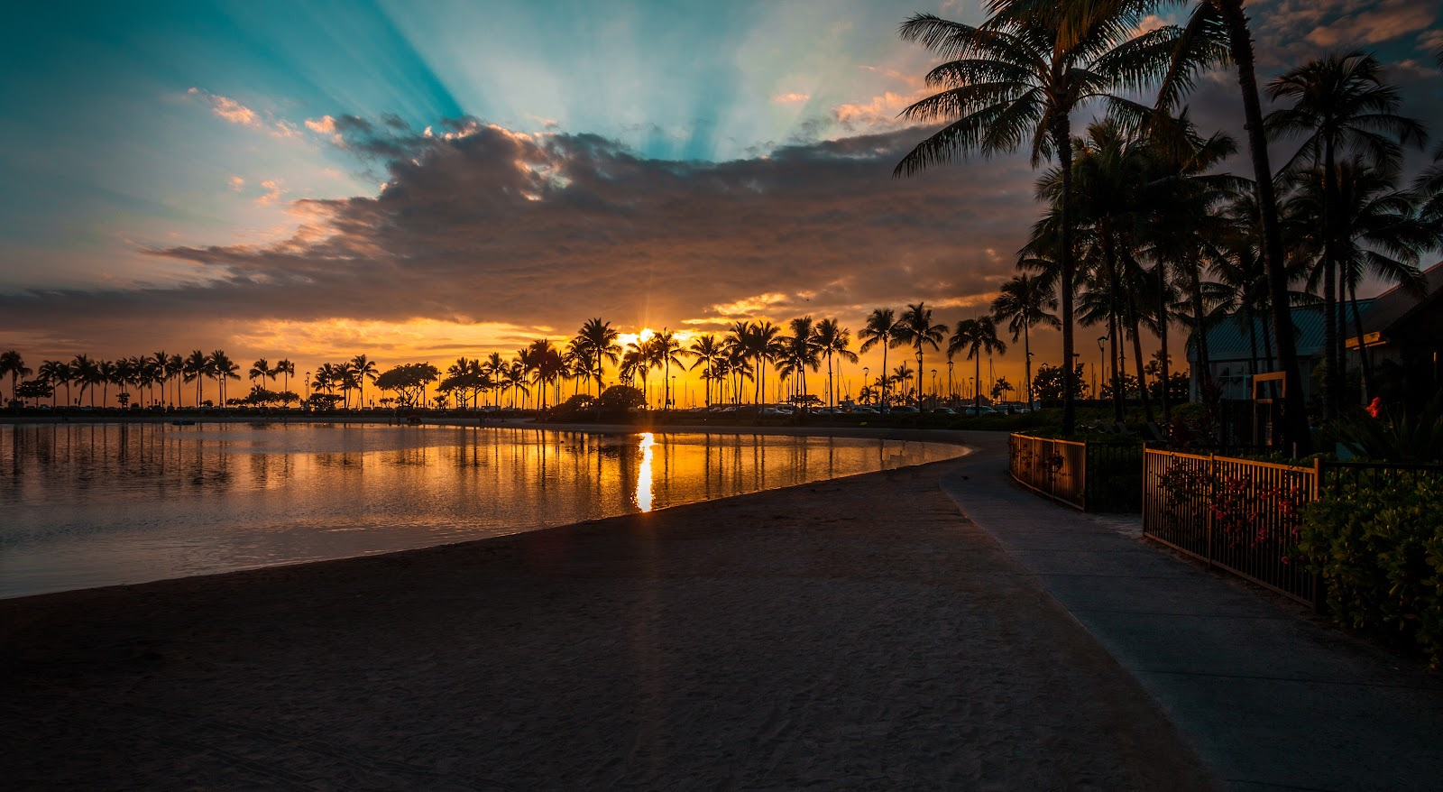A resort in Hawaii at sunset with palm trees