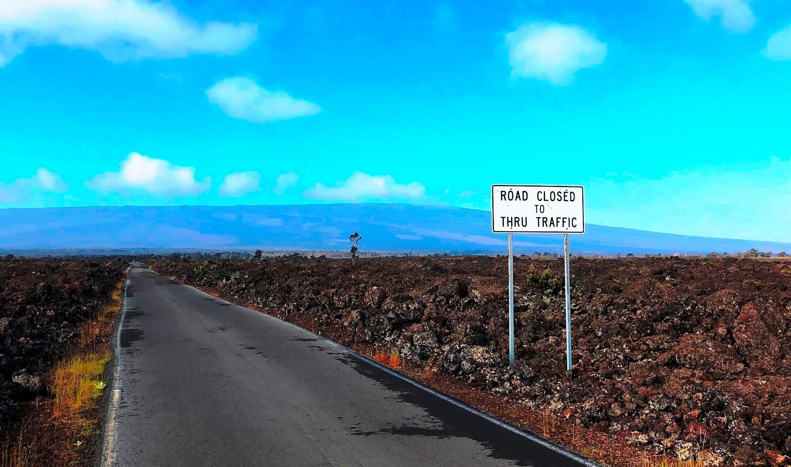 Cycling Mauna Loa Volcano - roadway, lava field and roadway sign