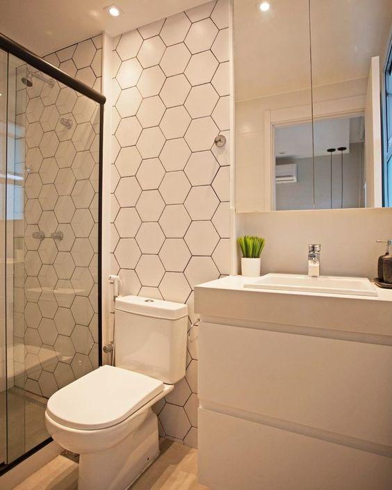 Banheiro com revestimento hexagonal branco na parede do box e vaso sanitário, armários brancos e piso amadeirado.