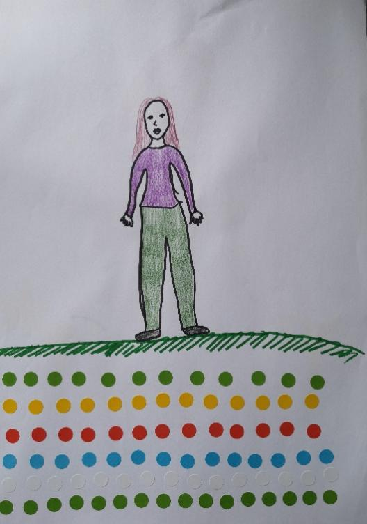 A woman with long hair standing on a filed of stickers arranged in rows by colour.