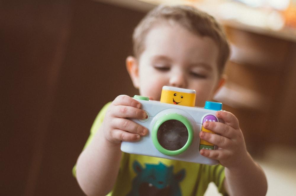 toddler holding white camera toy