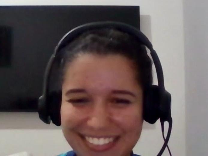 Foto de Dayana, uma mulher branca de cabelos escuros e presos. Na imagem ela está sorrindo e usando fones de ouvido extra auricular.