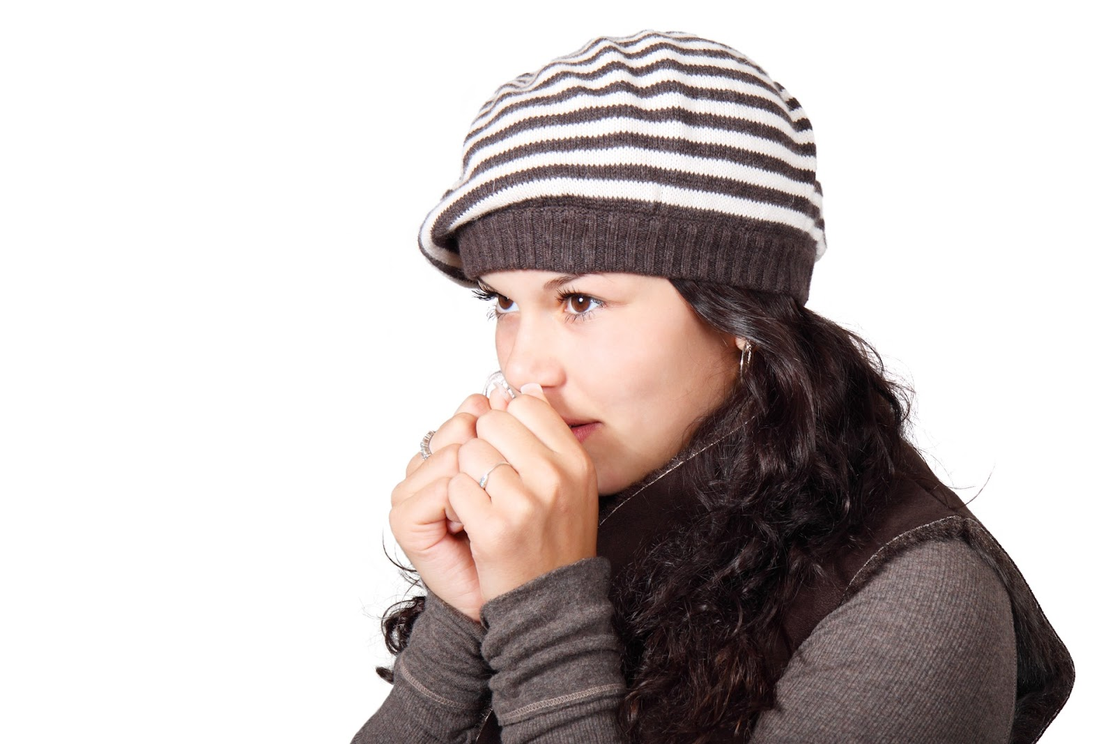 A woman wearing warm clothes appears to be blowing on her hands to warm them.