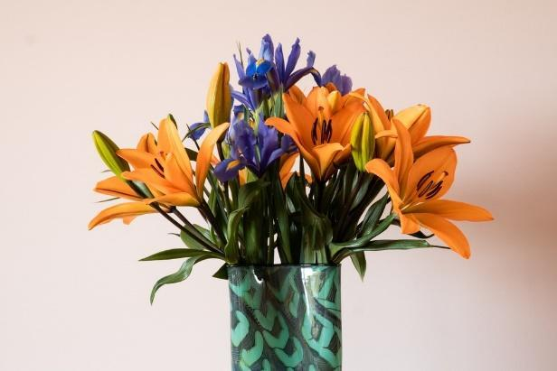 yellow and blue flowers in blue glass vase
