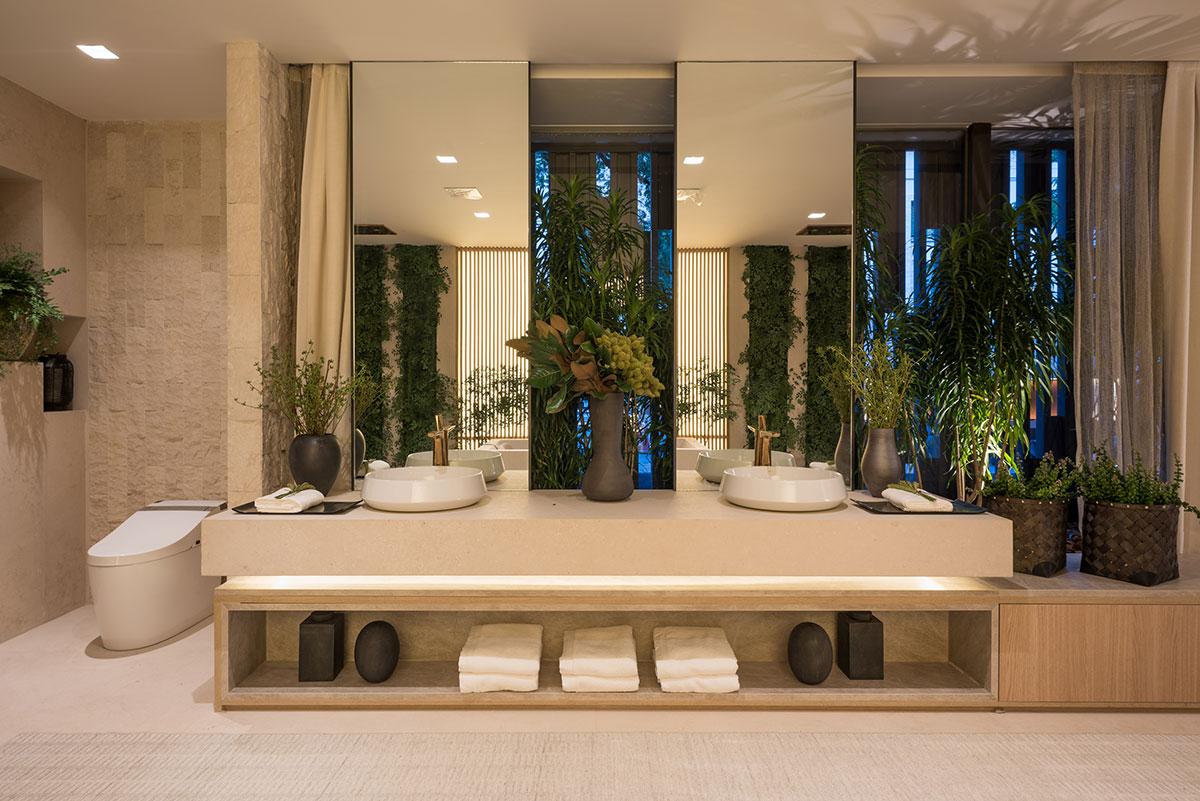 Banheiro com plantas, revestimento de pedras naturais na parede e pia de porcelanato com mobília de madeira.