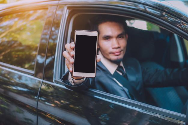 Motorista mostrando um celular para a câmera