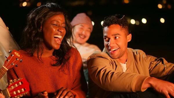 três amigos em um lual a noite cantando e se divertindo