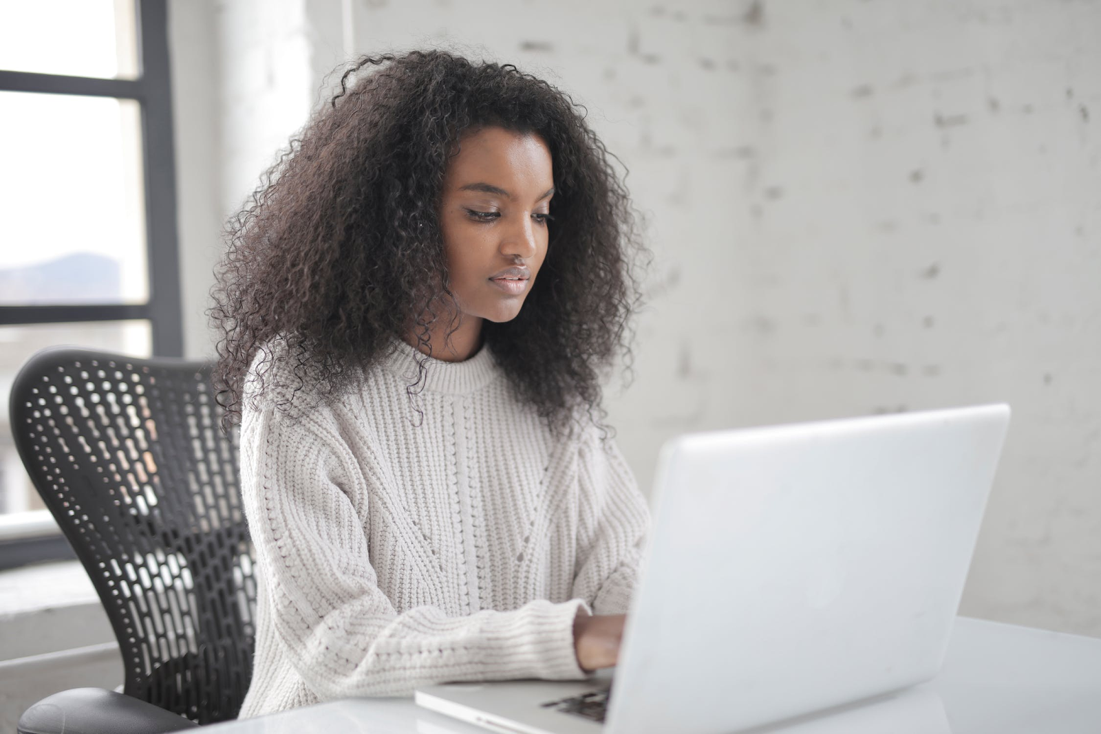 Woman wearing a white sweater using her laptop
