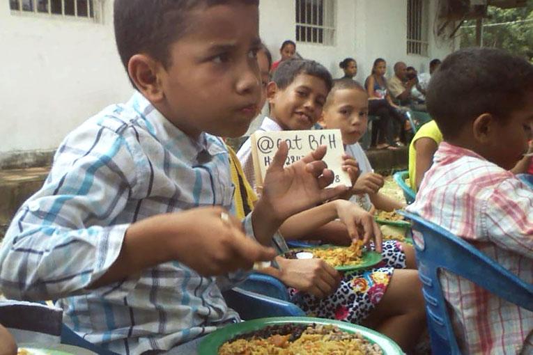 criança venezuelana comendo graças a doações de bitcoin cash