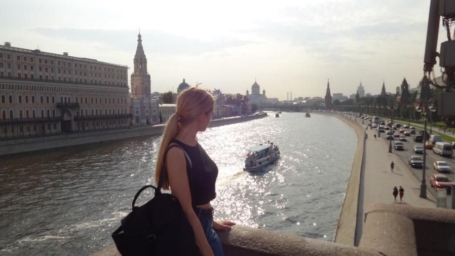 A person standing next to a body of water with buildings in the background  Description automatically generated