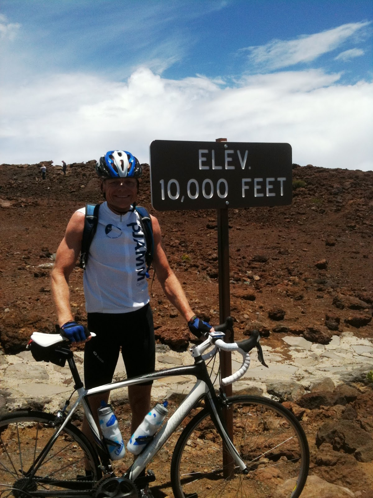 Climbing Haleakala Volcano  by bike - John Johnson with bike at 10,000' sign