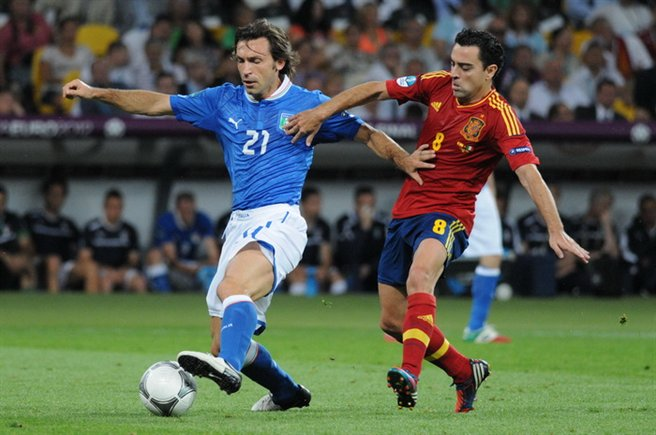 Pirlo on the ball and Xavi running by his side