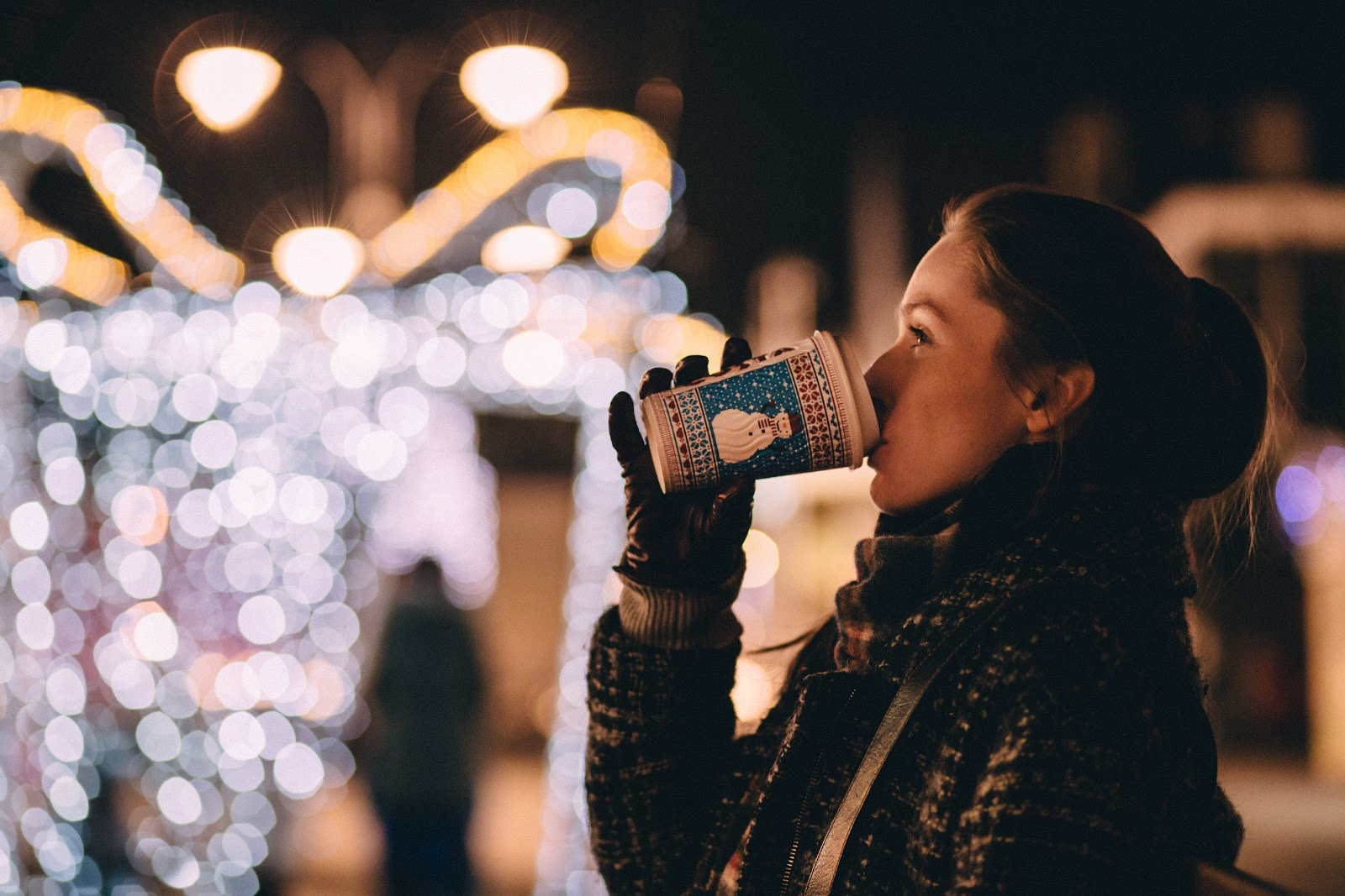 Woman drinking coffee looking at Christmas lights