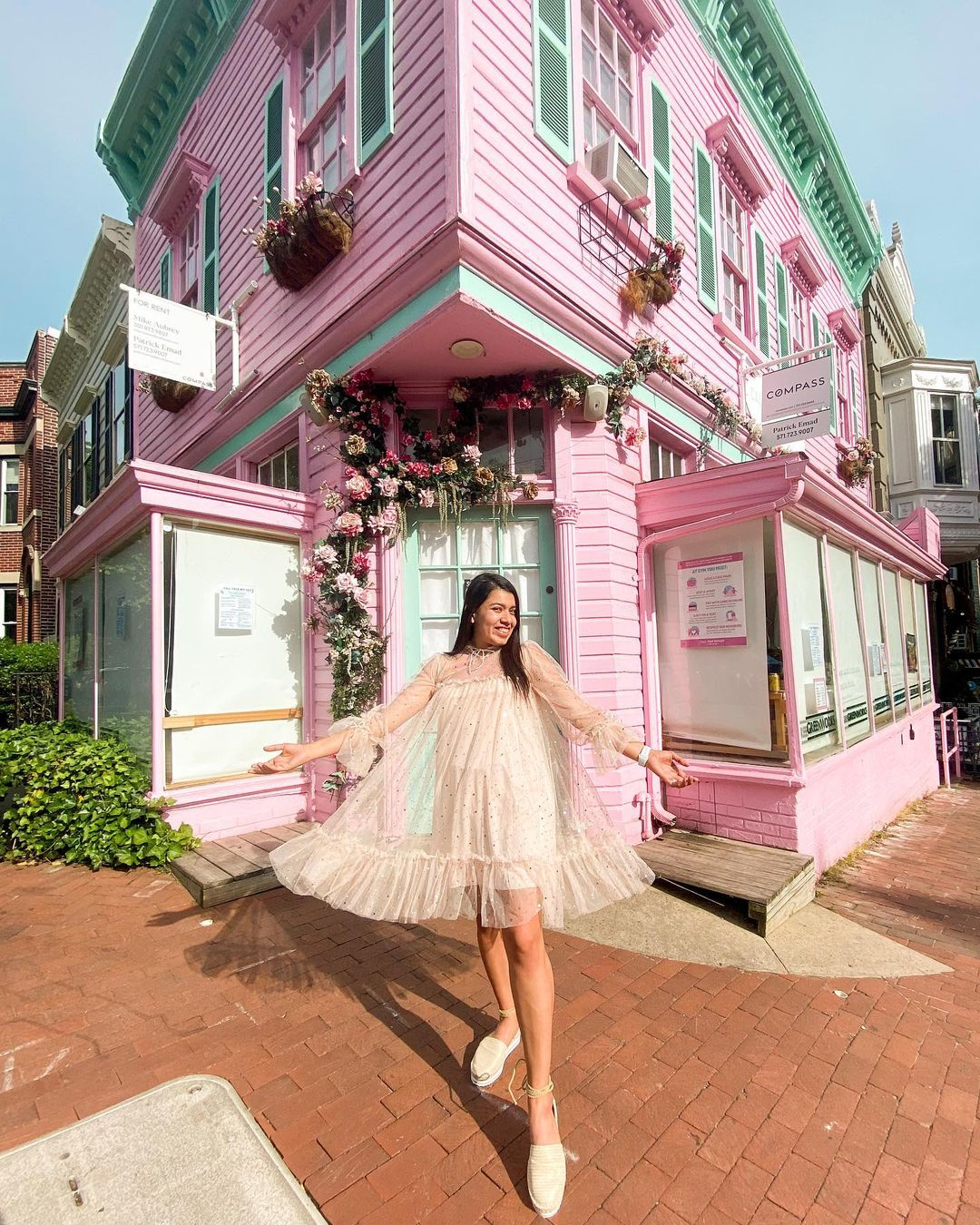 A woman in a beige dress in front of a house with pink and green siding.