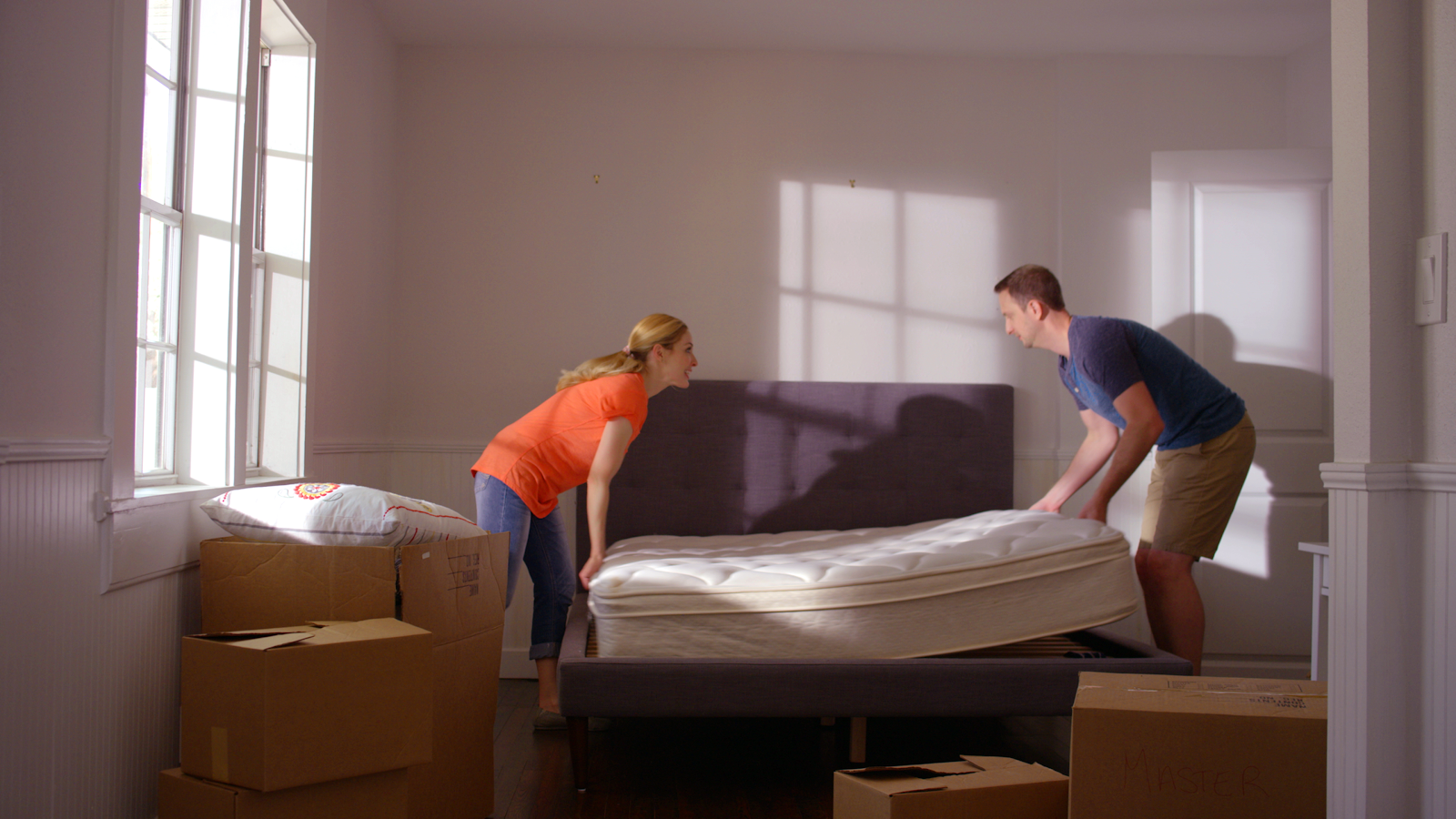 couple moving a mattress from the bedframe