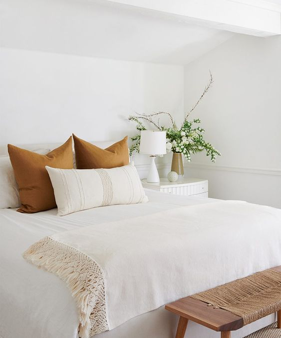 Bedroom setting mostly white with the exception of fall colored euro shams that pop.
