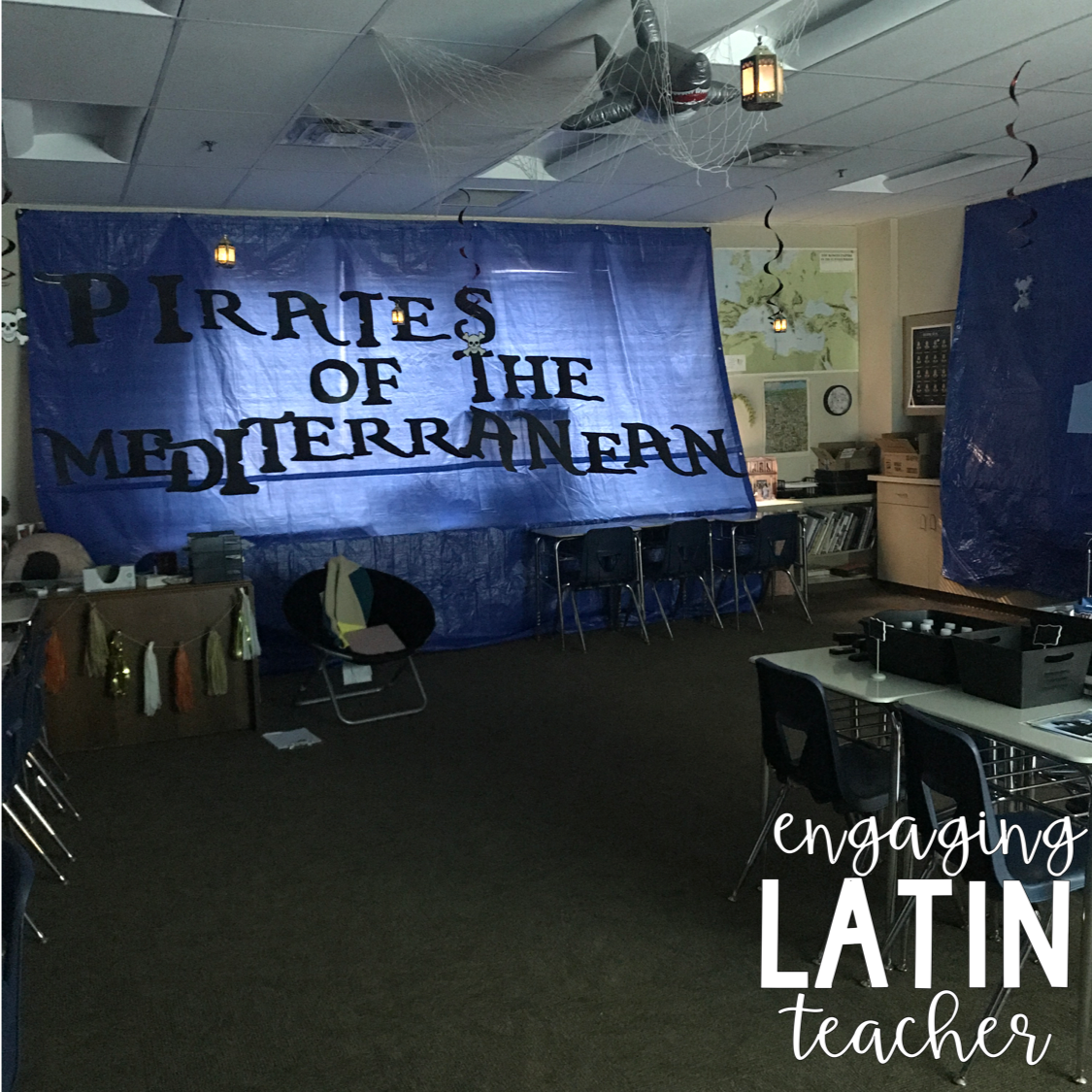 "Desks and chairs set up in table arrangements with large banner that reads ""Pirates of the Mediterranean"""