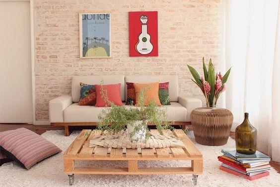 Sala rústica com mesa de centro de palete, sofá creme, vaso de planta de madeira e quadros decorativos.