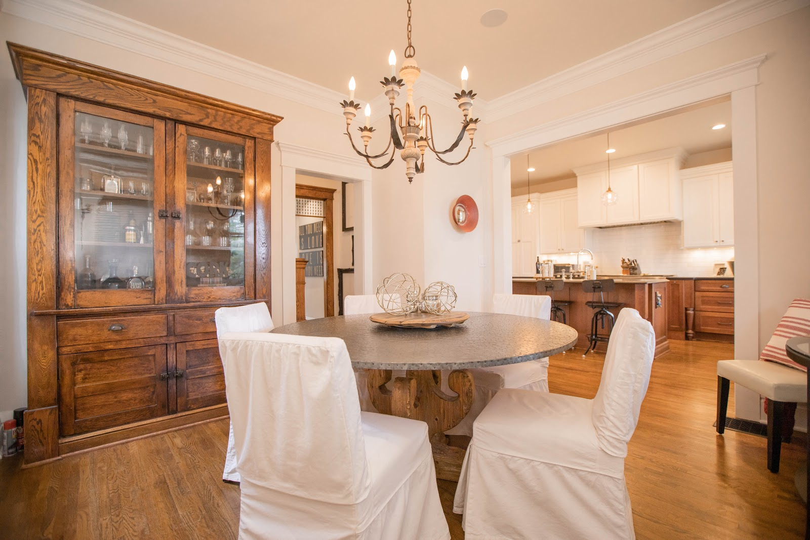 Dining area with white chairs and a chandelier