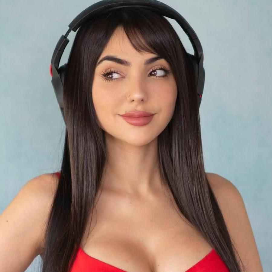 mulher branca tem cabelos pretos lisos e longos, veste blusa vermelha e está com fones de ouvido. Foto: Nivy Estephan Youtube.