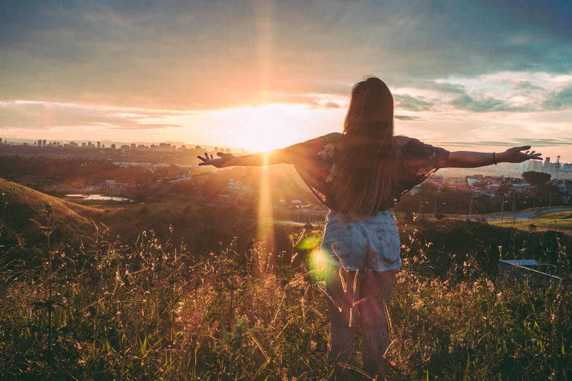 A person stands in a field at sunrise