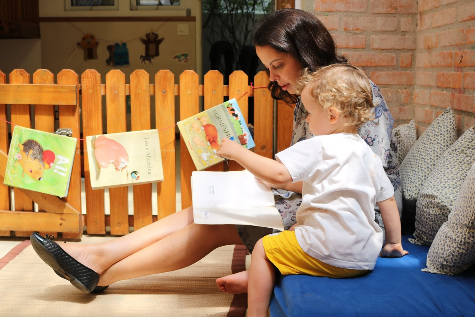 A imagem mostra um adulto lendo um livro, ao seu lado uma criança.