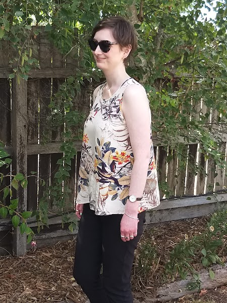 Siobhan stands in front of a garden fence. She wears a tank top with narrowed shoulders and slight scoop neck, in a beige printed rayon with slim-fit black pants. She is side on so you can see the voluminous tent shape of the top. She wears large tortoiseshell sunglasses and is smiling.