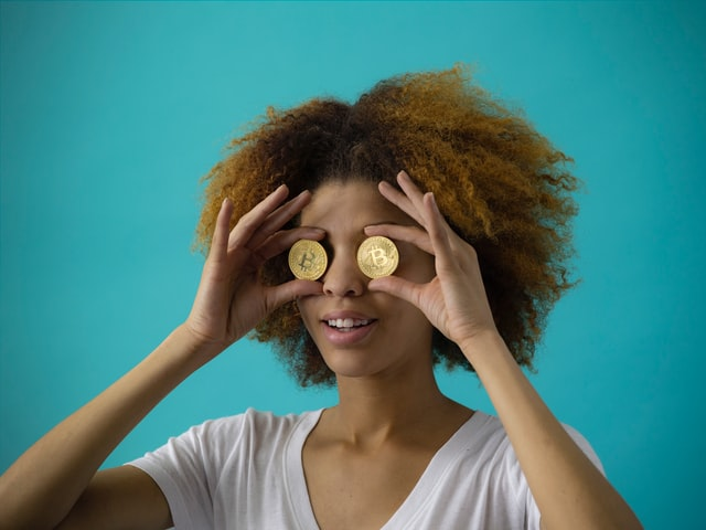 A woman holding up two pieces of Bitcoin and covering her eyes with them.