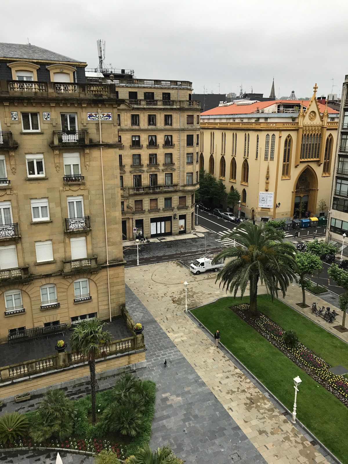 traditional spanish buildings, small square with a palm tree and church in background on a cloudy day. view from maria cristina hotel room in san sebastian spain