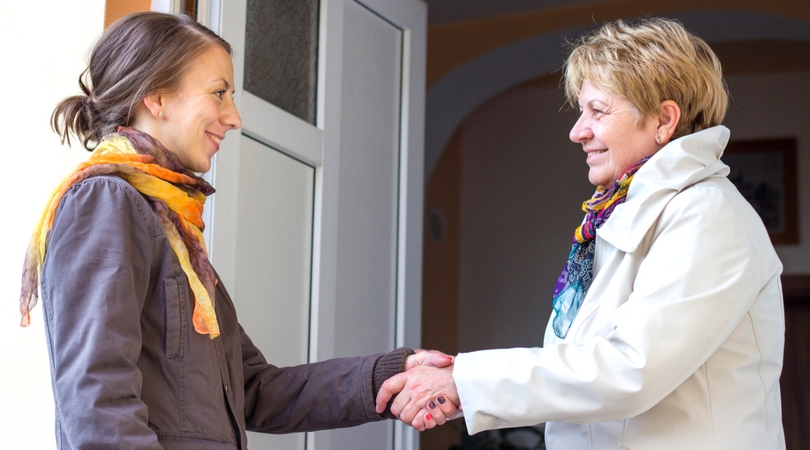 two women, presumably neighbors, shaking hands in a doorway