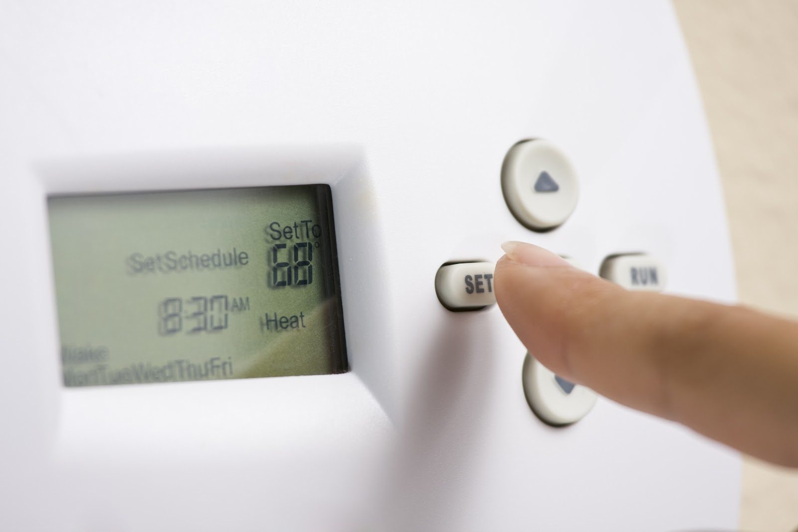 hand changing temperature on thermostat