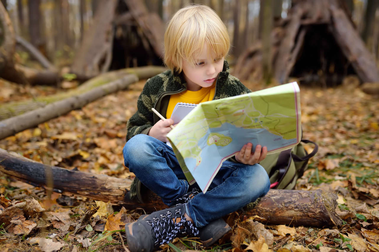 A child reading a map, one of the unplugged activities that benefit from these coding basics