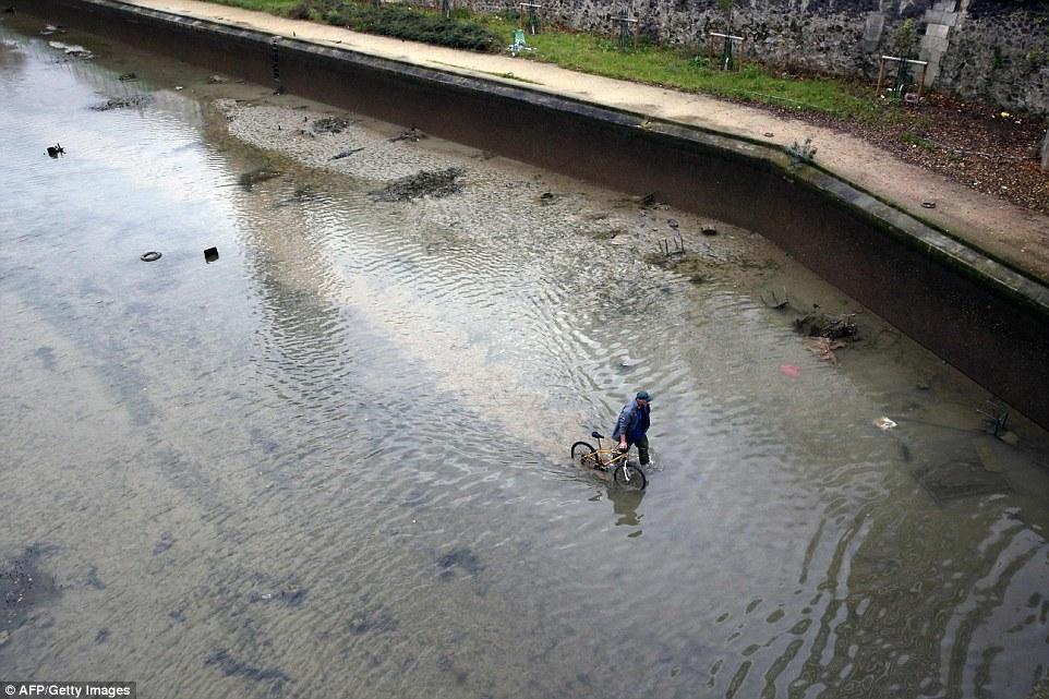 不尋常的旅程:在周四完全耗盡之前,一名男子在運河中的剩餘水中行走時騎車