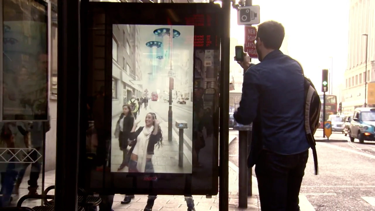 Pepsi Max bus shelter showing the AR windows experience with a person using their smartphone in front of it.
